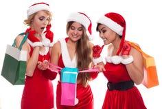 Mooie sexy meisjes die de kleren van de Kerstman met het shoping bedelaars dragen Stock Foto