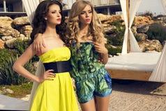 Mooie sexy meisjes in kleding die op strand stellen Stock Foto