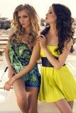 Mooie sexy meisjes in kleding die op strand stellen Royalty-vrije Stock Fotografie