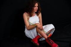 Mooie sexy meisjeszitting met witte sleeveless uniformjas, rode tennisschoenenlaarzen royalty-vrije stock fotografie