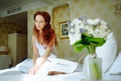 Mooie sexy redhairdame in elegante witte damesslipjes en peignoir Manierportret van model binnen Schoonheidsvrouw met kant linge stock fotografie
