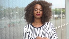 Mooie sexy sensuele jonge Afrikaanse Amerikaanse vrouw die charmingly op het van de achtergrond glasmuur close-up glimlachen