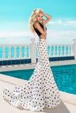 Mooie, sexy vrouw in een elegante stipkleding, die zich door de pool bevinden stock afbeeldingen