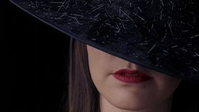 Mooie sexy vrouw in een zwarte heksenkostuum met rode lippen en een hoed, die naar de camera kijkt en glimlacht afsluiten stock video