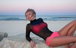Mooie sexy vrouw in modieuze zwempakzitting op rotsen dichtbij het overzees stock afbeeldingen