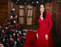 Mooie sexy vrouw in rode kleding die zich binnen bevinden Stock Foto's