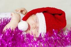 Mooie slaapbaby in de hoed van het Nieuwjaar onder lovertje Stock Foto