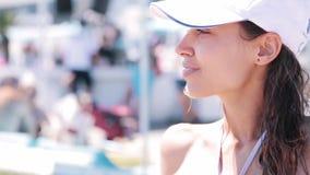 Mooie slanke jonge vrouw in bikini en wit honkbal GLB op de kust met blauwe hemel tegen kuuroordhotel Gelukkig wijfje stock video