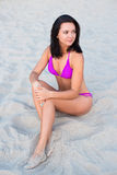 Mooie slanke sexy vrouw in bikinizitting op strand Royalty-vrije Stock Fotografie