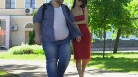 Mooie slanke vrouw in de rode handen van de kledingsholding met zwaarlijvige vriend, droom stock videobeelden