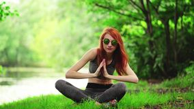 Mooie slanke vrouw het praktizeren yoga in park stock footage