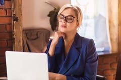 Mooie slimme bedrijfsvrouwenzitting bij de lijst bij werkstation met laptop stock fotografie