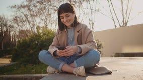 Mooie smartphone van het vrouwengebruik in park stock videobeelden
