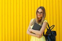 Mooie smileystudente met boek die grappig stuk speelgoed om gla dragen royalty-vrije stock afbeeldingen