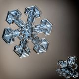 Mooie sneeuwvlok op lichtoranje dichte omhooggaand als achtergrond stock foto