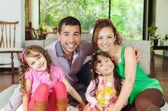 Mooie Spaanse familie van vier die op vloer zitten Royalty-vrije Stock Foto