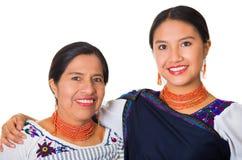 Mooie Spaanse moeder en dochter die traditionele Andeskleding dragen, die terwijl samen het stellen gelukkig omhelzen Stock Foto's