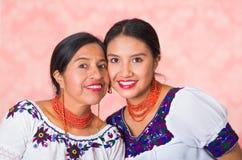 Mooie Spaanse moeder en dochter die traditionele Andeskleding dragen, die terwijl samen het stellen gelukkig omhelzen Royalty-vrije Stock Fotografie