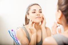 Mooie Spaanse vrouw die een spiegel bekijken royalty-vrije stock afbeeldingen