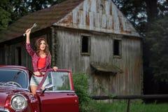 Mooie speld op meisje die hulp nodig hebben, die een stakker houden, die zich dichtbij retro auto bevinden royalty-vrije stock foto