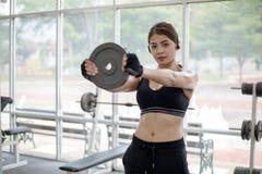 Mooie spier geschikte vrouw die de bouwspieren en pasvorm uitoefenen Royalty-vrije Stock Fotografie