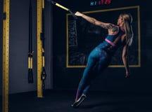 Mooie spierblondevrouw in sportkleding met een tatoegering op haar wapen die oefening met TRX-systeem doen bij gymnastiek royalty-vrije stock fotografie