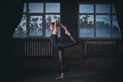 Mooie sportieve geschikte van de de praktijkenyoga van de yogivrouw asana Natarajasana - Lord Of The Dance stelt in de donkere za Stock Afbeeldingen