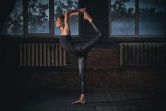Mooie sportieve geschikte van de de praktijkenyoga van de yogivrouw asana Natarajasana - Lord Of The Dance stelt in de donkere za Royalty-vrije Stock Fotografie