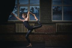 Mooie sportieve geschikte van de de praktijkenyoga van de yogivrouw asana Natarajasana - Lord Of The Dance stelt in de donkere za Stock Afbeelding