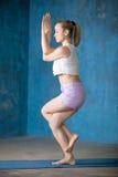 Mooie sportieve jonge vrouw die Garudasana-houding doen Royalty-vrije Stock Afbeelding