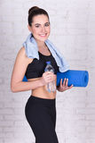 Mooie sportieve vrouw met yogamat die zich over witte baksteen w bevinden Stock Fotografie