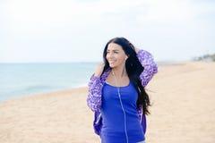 Mooie sportieve vrouwen gelukkige glimlach en het luisteren muziek op het strand royalty-vrije stock afbeeldingen