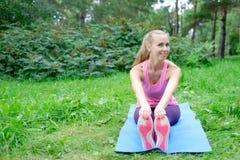 Mooie sportvrouw die uitrekkende fitness oefening in stadspark doen bij groen gras Yogahoudingen royalty-vrije stock foto