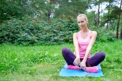 Mooie sportvrouw die uitrekkende fitness oefening in stadspark doen bij groen gras Yogahoudingen stock foto's