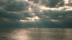 Mooie stralen van zon het breken door de wolken over het wateroverzees of het grote meer en de boot stock videobeelden