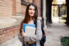 Mooie student die bij camera buiten op campus bij de universiteit glimlachen Royalty-vrije Stock Afbeeldingen