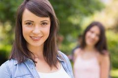 Mooie student die bij camera buiten op campus glimlachen Stock Afbeelding