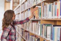 Mooie student die boek plaatsen in plank stock afbeeldingen