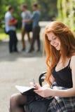 Mooie student die buiten op campus bestuderen Stock Afbeelding