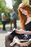Mooie student die buiten op campus bestuderen Stock Foto