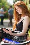 Mooie student die buiten op campus bestuderen Stock Afbeeldingen