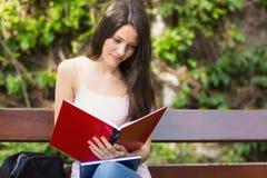 Mooie student die buiten op campus bestuderen Stock Fotografie