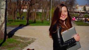 Mooie student die met laptop lopen, van goed winderig weer genieten en camera bekijken stock video