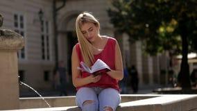 Mooie student in roze t-shirt en jeans die boek lezen dichtbij fontein stock video