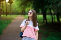 Mooie studentenmeisje het drinken koffie bij de zomerpark royalty-vrije stock fotografie