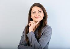 Mooie succes bedrijfsvrouw in kostuum met vinger onder het gezicht die en omhoog op blauwe achtergrond denken kijken close-up stock afbeelding