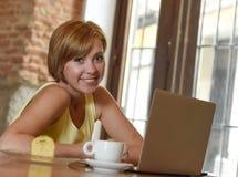 Mooie succesvolle vrouw die bij koffiewinkel werken met laptop computer die koffie van kop genieten Royalty-vrije Stock Afbeeldingen
