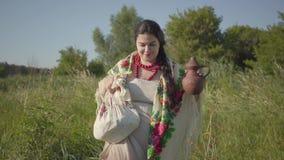 Mooie te zware vrouw die in wild hoog gras met de aarden kruik op het groene de zomergebied lopen Mooi stock video