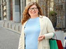 Mooie te zware vrouw met het winkelen zakken Stock Afbeelding