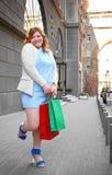 Mooie te zware vrouw met het winkelen zakken Royalty-vrije Stock Foto's